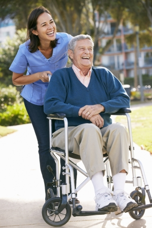 care at home: Carer Pushing Senior Man In Wheelchair Stock Photo
