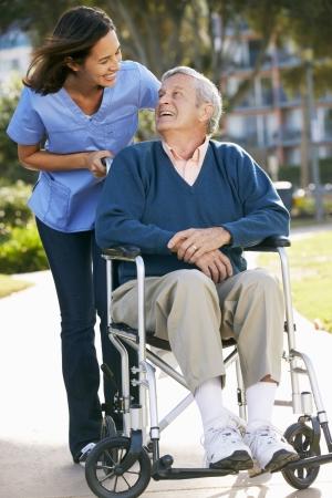 persona en silla de ruedas: Carer Empujar hombre mayor en silla de ruedas Foto de archivo