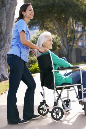 Carer Pushing Senior Woman In Wheelchair photo
