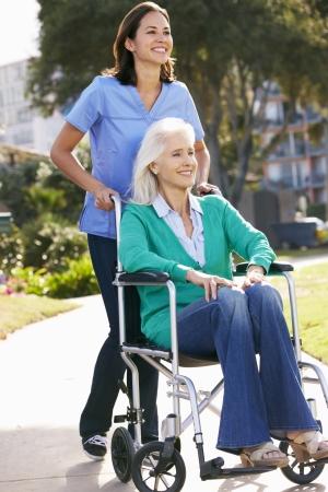 cadeira de rodas: Cuidador empurr�o da mulher s�nior na cadeira de rodas
