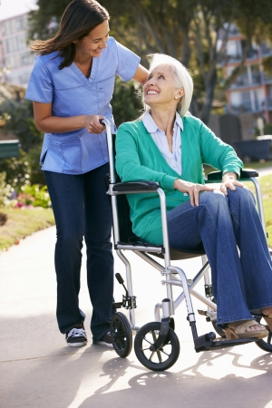 disabled person: Carer Pushing Senior Woman In Wheelchair