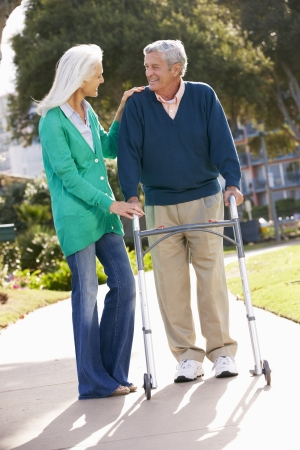 carer: Senior Woman Helping Husband With Walking Frame