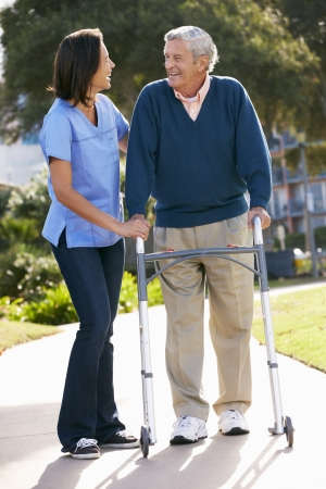 home garden: Carer Helping Senior Man With Walking Frame Stock Photo