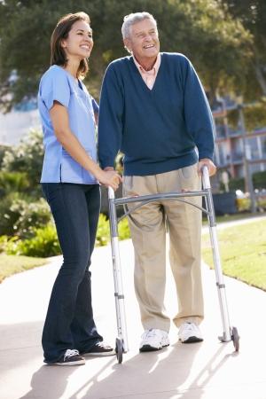 senioren wandelen: Verzorger Helpen Senior Man Met looprek Stockfoto