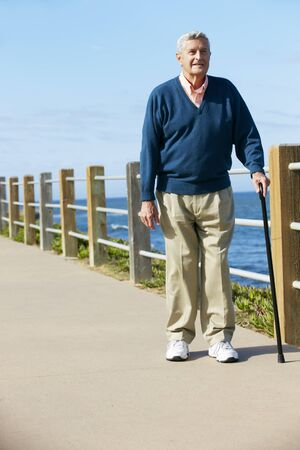 guy with walking stick: Senior Man Walking Along Path By The Sea