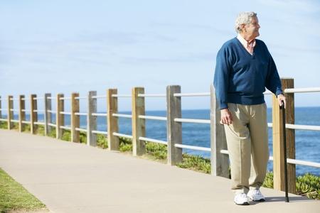 and the horizontal man: Senior Man Walking Along Path By The Sea