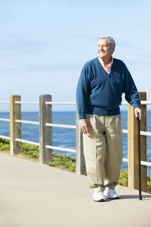adult 80s: Senior Man Walking Along Path By The Sea