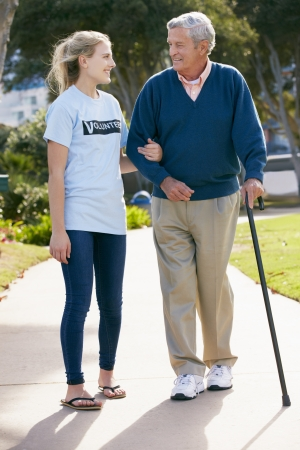 guy with walking stick: Teenage Volunteer Helping Senior Man Walking Through Park