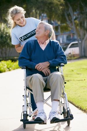 Teenage Volunteer Pushing Senior Man In Wheelchair photo