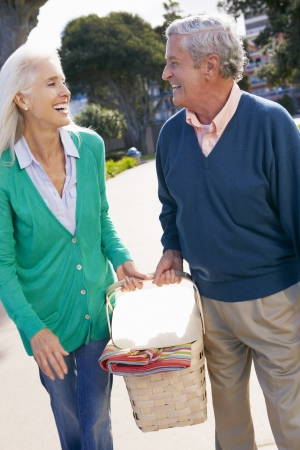 adult 80s: Senior Couple Walking In Park Together With Picnic Basket
