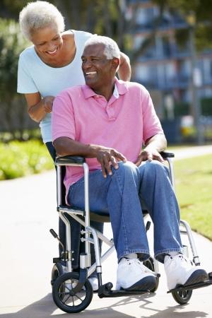 personas discapacitadas: Mujer mayor empuje marido en silla de ruedas Foto de archivo