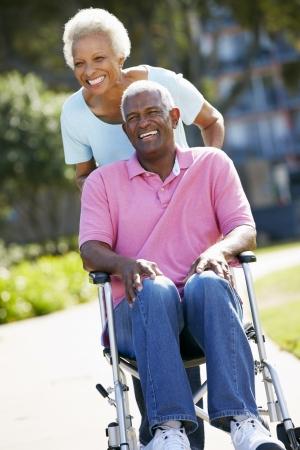 Mujer mayor empuje marido en silla de ruedas