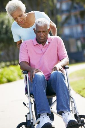 Mujer mayor empuje marido infeliz en silla de ruedas
