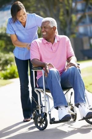 Carer Pushing Senior Man In Wheelchair photo