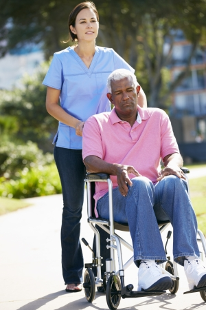 Carer Pushing Unhappy Senior Man In Wheelchair photo