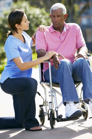 consoling: Carer Pushing Unhappy Senior Man In Wheelchair