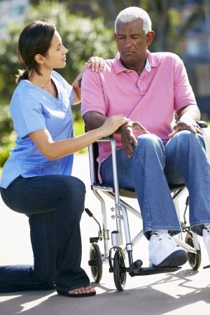 senior depression: Carer Pushing Unhappy Senior Man In Wheelchair