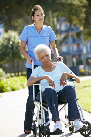 Carer Pushing Unhappy Senior Woman In Wheelchair Stock Photo - 18736756