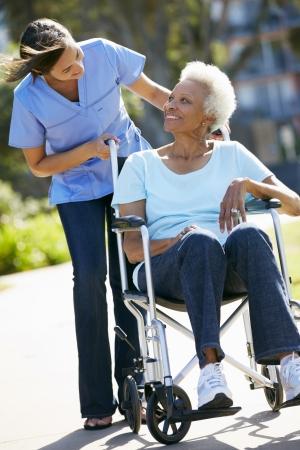 Carer Empujar mujer mayor en silla de ruedas