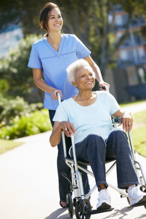 assisted living: Carer Pushing Senior Woman In Wheelchair
