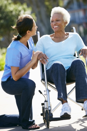 persona en silla de ruedas: Carer Empujar mujer mayor en silla de ruedas