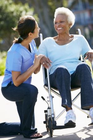 black nurse: Carer Pushing Senior Woman In Wheelchair