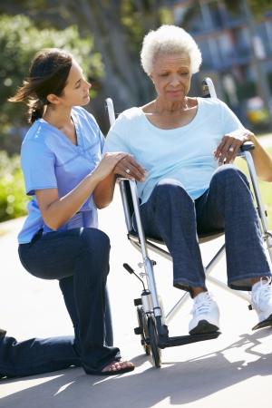 worried woman: Carer Pushing Unhappy Senior Woman In Wheelchair