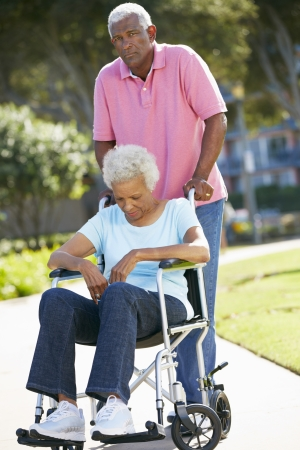 Senior Woman Pushing Unhappy Husband In Wheelchair Stock Photo