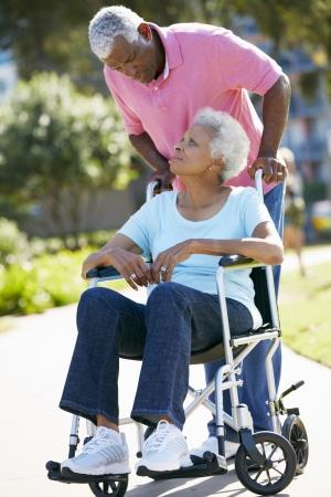 Senior Vrouw Duwen Ongelukkig man in rolstoel Stockfoto