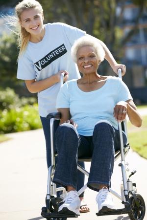 the ageing process: Teenage Volunteer Pushing Senior Woman In Wheelchair