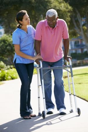 Carer ayudar al hombre mayor con un andador