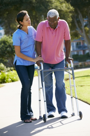 the ageing process: Carer Helping Senior Man With Walking Frame Stock Photo
