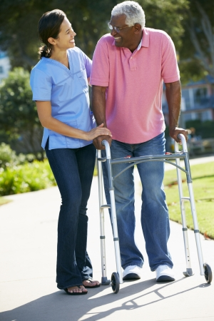 home help: Carer Helping Senior Man With Walking Frame Stock Photo