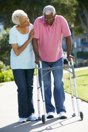 black nurse: Senior Woman Helping Husband With Walking Frame
