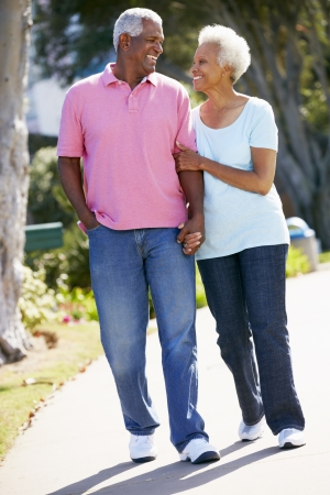 healthy seniors: Senior Couple Walking In Park Together Stock Photo