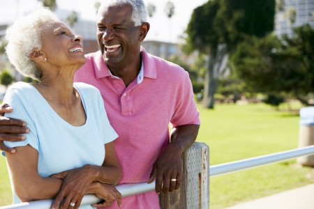 two women talking: Senior Couple Walking In Park Together Stock Photo