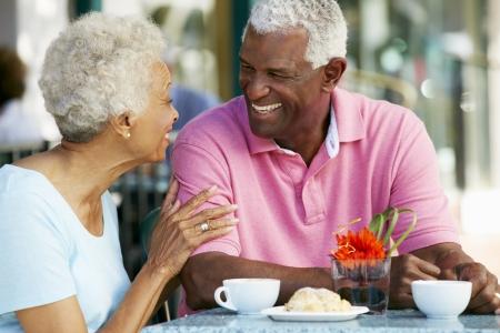 pareja comiendo: Senior pareja al aire libre Disfrutando de un aperitivo en Caf