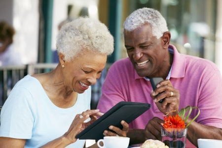 cell phone: Senior Couple Using Tablet Computer At Outdoor Caf� Stock Photo