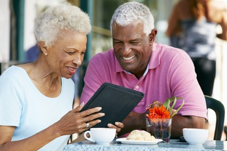 elderly couples: Senior Couple Using Tablet Computer At Outdoor Caf� Stock Photo