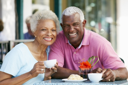 tea hot drink: Senior Couple Enjoying Snack At Outdoor Café Stock Photo
