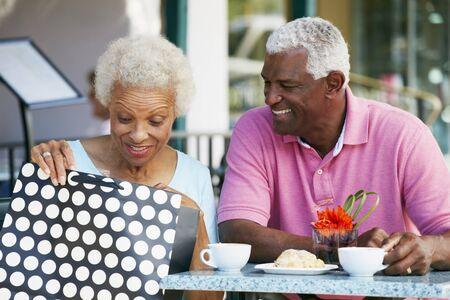 Senior Couple Enjoying Snack At Outdoor Café After Shopping photo