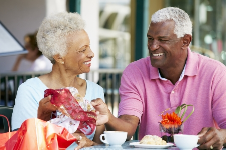 after shopping: Senior Couple Enjoying Snack At Outdoor Caf� After Shopping
