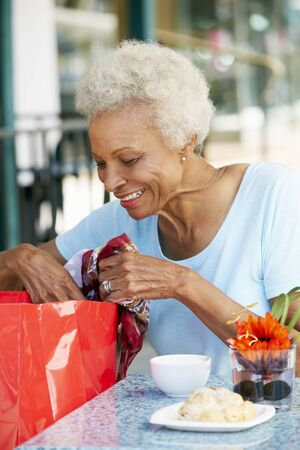 Senior Woman Enjoying Snack At Outdoor Caf� After Shopping photo