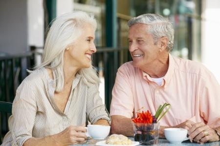 happy retirement: Senior Couple Enjoying Snack At Outdoor Caf� Stock Photo
