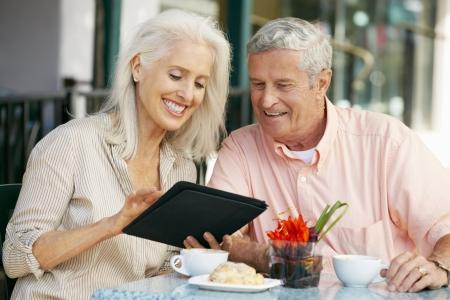 senior ordinateur: Couple Senior Utiliser l'ordinateur tablette Au Caf ext�rieure