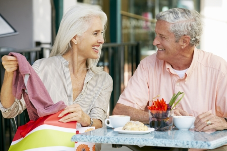Senior Couple Enjoying Snack At Outdoor Café After Shopping photo