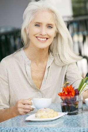 Senior Woman Enjoying Snack At Outdoor Caf� photo