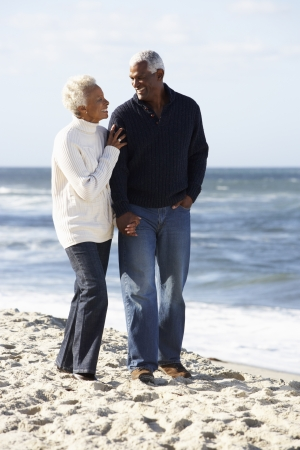 african american couple: Senior Couple Walking Along Beach Together