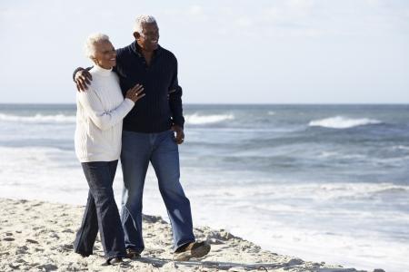 senioren wandelen: Senior Paar wandelen langs strand samen Stockfoto