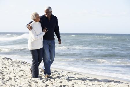 senioren wandelen: Hoger Paar dat langs Strand samen